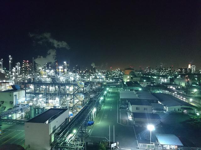 Eine Fabrik bei Nacht leuchtet hell unter dem Nachthimmel.